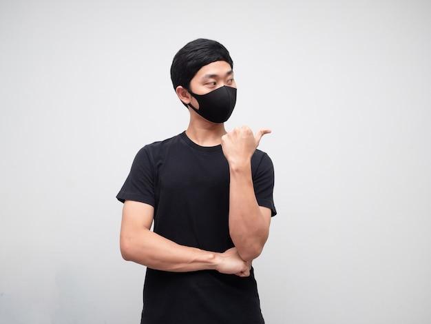 Porträtmann mit maske zeigt mit dem finger und schaut auf die rechte seite auf weißem hintergrund