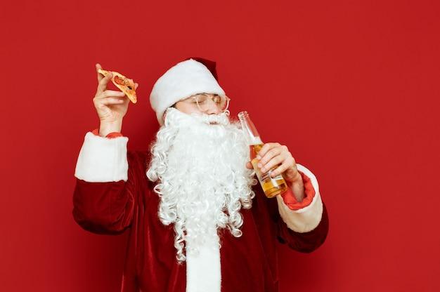 Porträtmann verkleidet als weihnachtsmann, der flasche bier und stück pizza hält