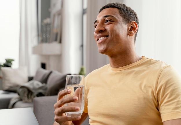 Porträtmann zu hause, der glas wasser trinkt