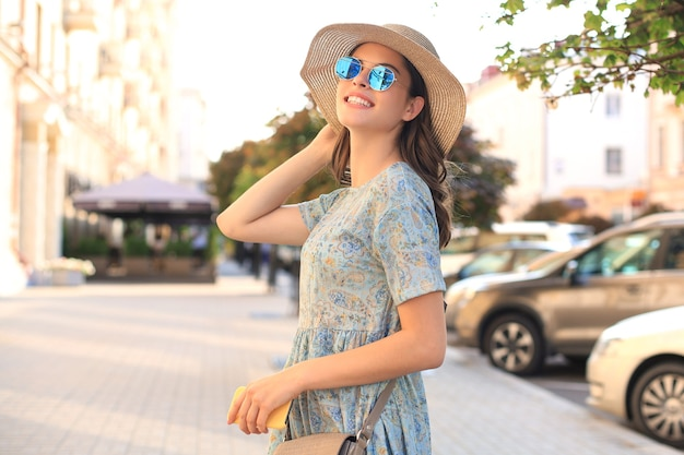Porträtmodefrau im blauen kleid mit sonnenbrille, die auf die straße geht und smartphone in der hand hält.