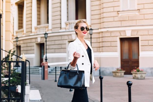 Porträtmodefrau in der sonnenbrille, die auf straße geht. sie lächelt zur seite.