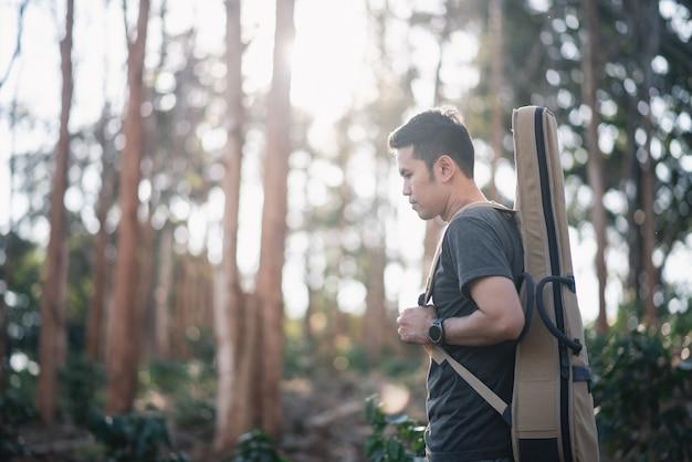 Porträtmusikermann mit gitarre am forrest