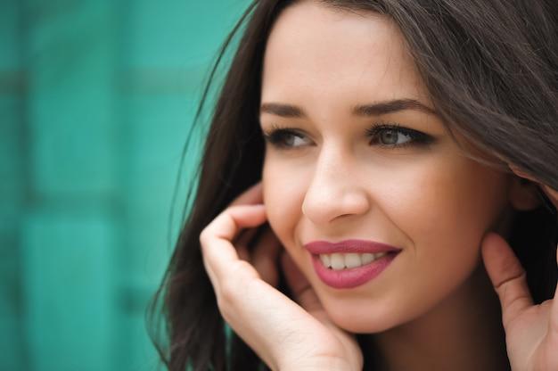 Porträtnahaufnahme der jungen schönen frau, auf grünem hintergrundsommernatur