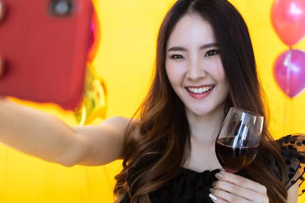Porträtnahaufnahme der lächelnden schönen jungen asiatischen frau, die ein selfiefoto mit dem mobilen smartphone macht und ein glas rotwein mit gelber wand und farbenvoller ballonparty hält.