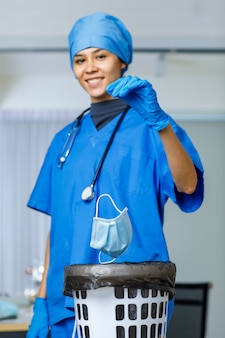 Porträtnahaufnahme einer gebrauchten chirurgischen gesichtsmaske, die von der glücklichen, hübschen weiblichen freiheitsdoktorhand in blauem krankenhausanzug mit einem lächelnden blick auf die kamera des stethoskops während des endes der covid-pandemie abgeworfen wurde