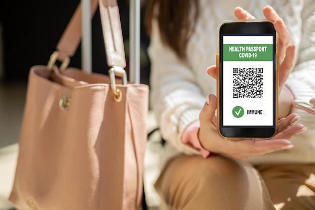 Porträtreisefrau in gesichtsmaske mit digitalem app-gesundheitspass-kovid-qr-code auf smartphone
