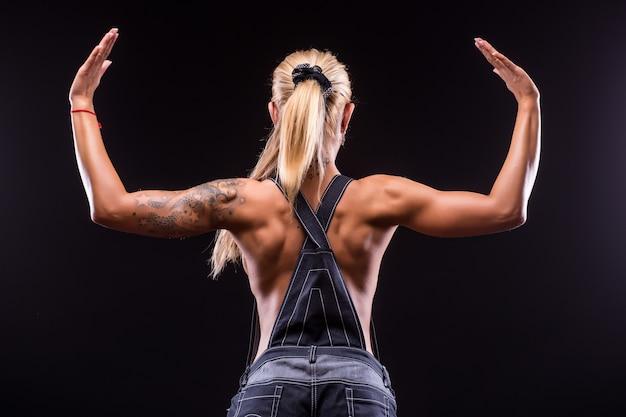 Porträtrückansicht einer schönen athletischen frau auf dunkelheit
