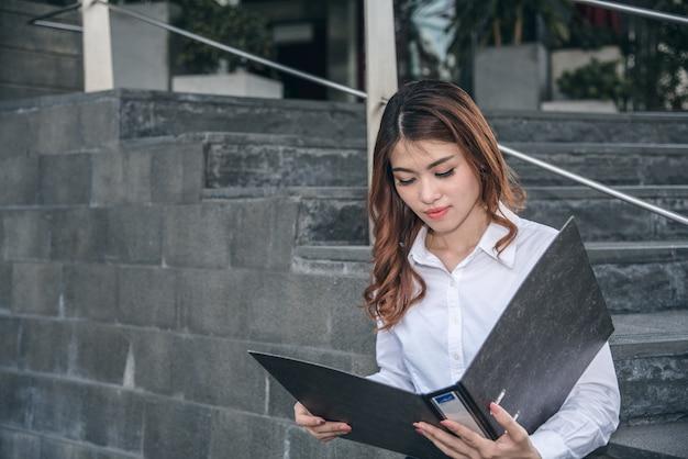 Porträts der schönen asiatischen frau im denkenden ausdruck, der mit finanzdiagrammdokument arbeitet