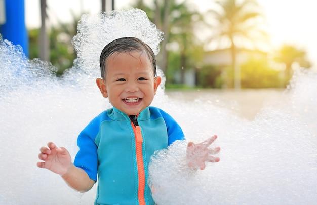 Porträts des glücklichen kleinen asiatischen jungen lächelnd, der spaß in der schaumparty am pool im freien hat.