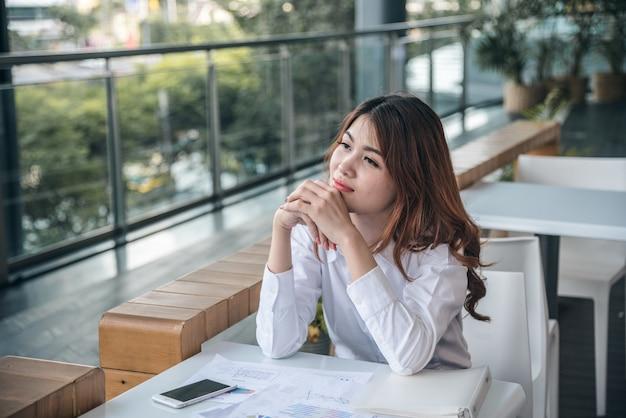 Porträts des schönen asiatischen frauenblickes nett und vertrauen sitzt und fühlt erfolg mit arbeit.