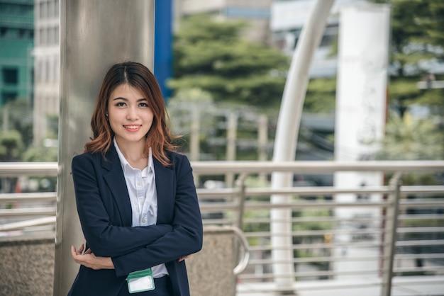 Porträts des schönen asiatischen frauenblickes nett und vertrauen steht herein draußen
