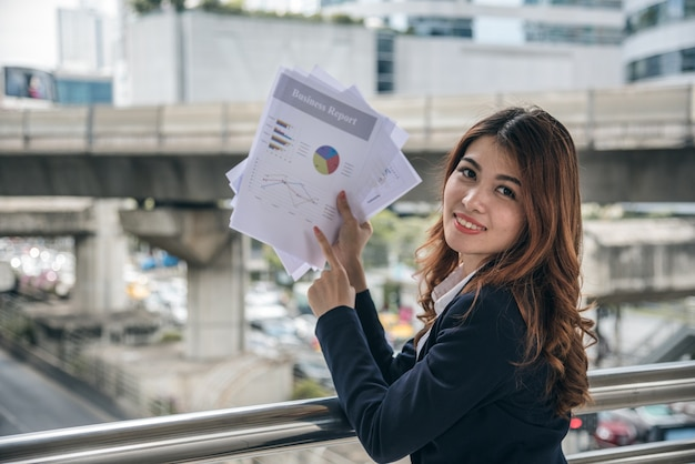 Porträts des schönen asiatischen frauenblickes nett und vertrauen steht und hält papierarbeit