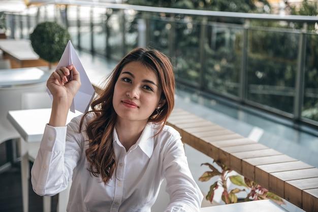 Porträts des schönen asiatischen frauenblickvertrauens steht und hält papierfläche