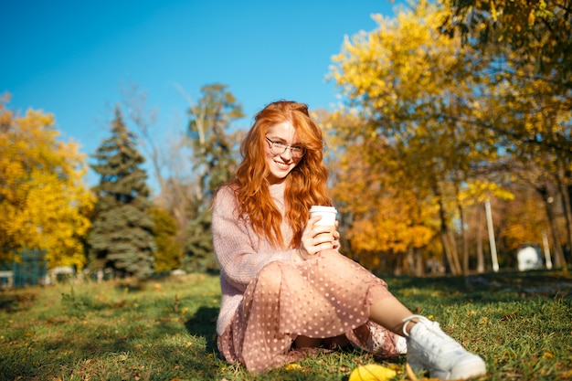 Porträts eines charmanten rothaarigen mädchens mit brille und hübschem gesicht. mädchen, das im herbstpark in einem pullover und in einem rock der korallenfarbe aufwirft.