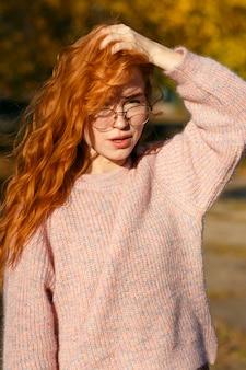 Porträts eines charmanten rothaarigen mädchens mit brille und süßem gesicht. mädchen, das im herbstpark in einem pullover und in einem korallenfarbenen rock aufwirft. das mädchen hat eine wundervolle stimmung