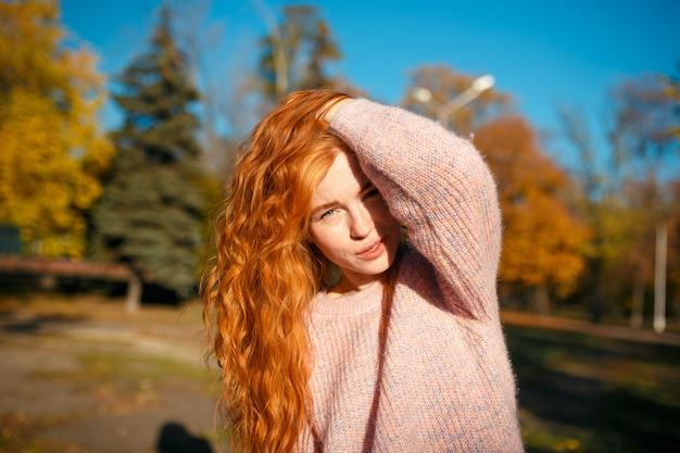 Porträts eines charmanten rothaarigen mädchens mit einem niedlichen gesicht. mädchen, das im herbstpark in einem pullover und in einem korallenfarbenen rock aufwirft. das mädchen hat eine wundervolle stimmung