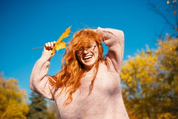 Porträts eines charmanten rothaarigen mädchens mit einem niedlichen gesicht. mädchen, das im herbstpark in einem pullover und in einem korallenfarbenen rock aufwirft. in den händen eines mädchens ein gelbes blatt