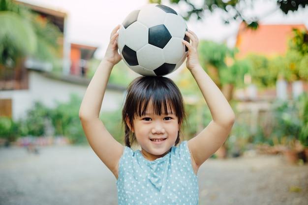 Porträts von kindern spielen gerne fußball, um sport zu treiben.