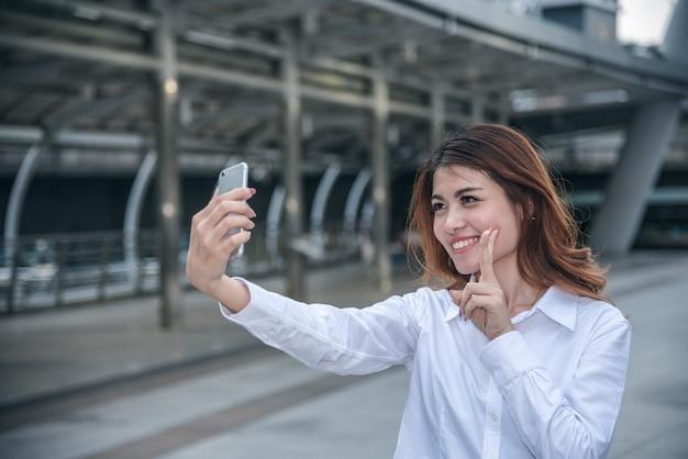 Porträts von pretty beautiful asiatin, die ein foto durch selfie in städtischem macht.