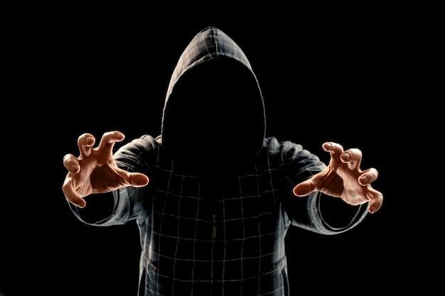 Porträtschattenbild eines mannes in einer haube auf einem schwarzen hintergrund sein gesicht ist nicht sichtbar