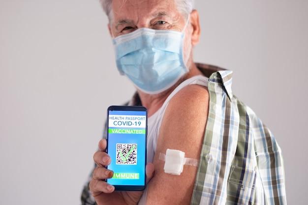 Porträtstudioaufnahme eines alten kaukasischen seniorenpatienten mit gesichtsmaske, der nach der dritten dosis des covid-19-coronavirus-impfstoffs eine grüne pass-app zeigt, mit blick auf die kamera