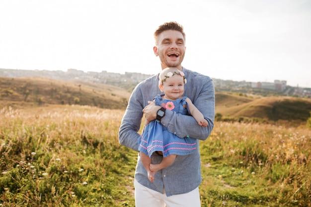 Porträtvater mit kind zusammen. papa umarmt kleine tochter im freien. junger vater mit baby gehen in feld. familiensommerferien. vater umarmt baby in der natur.