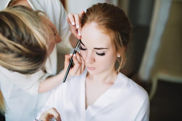 Porträtvorbereitung der braut am morgen vor der hochzeit. künstler macht make-up und sie hält die augen geschlossen