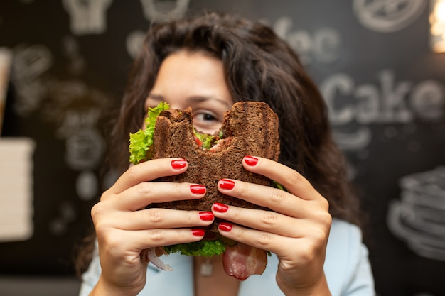 Portrai der jungen kaukasischen brunettefrau, die durch gebissenes sandwich schaut