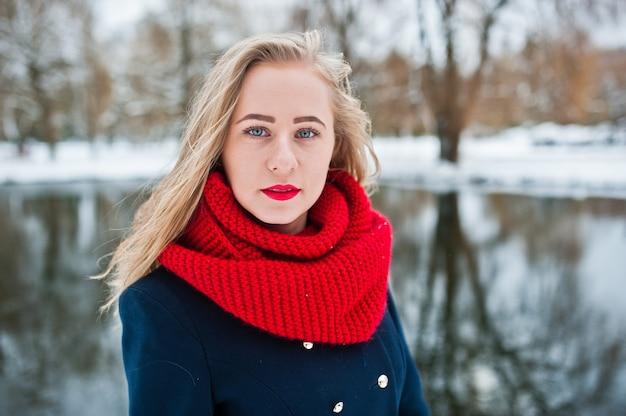 Portrai des blonden mädchens im roten schal und im mantel gegen gefrorenen see am wintertag.