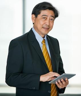 Portrait 50er jahre asiatische männliche führungskraft visionärer geschäftsinhaber, der formellen anzug und krawatte trägt, innenbüro steht, technologietablett verwendet, den bildschirm berührt, selbstbewusst und zuverlässig lächelt.