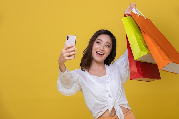 Portrait asiatische schöne glückliche junge frau mit sonnenbrille, die fröhlich lächelt und sie hält smartphone für selfie und online-shopping mit einkaufstüten auf gelbem hintergrund.