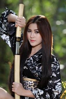 Portrait asien schöne japanische kimonofrau und japanische geishafrau mit japanischem schwert und woma