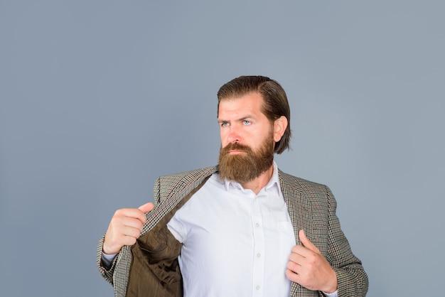 Portrait charmante reifer geschäftsmann im anzug auf grauem hintergrund isoliert gekleidet eleganter mann