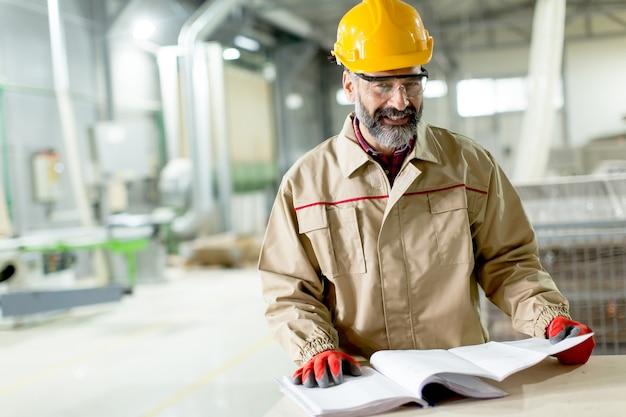 Portrait der älteren aufsichtskraft, die in der fabrik projest betrachtet
