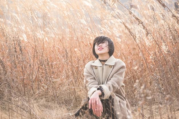 Portrait der artfrau, die unter reedfeld sitzt