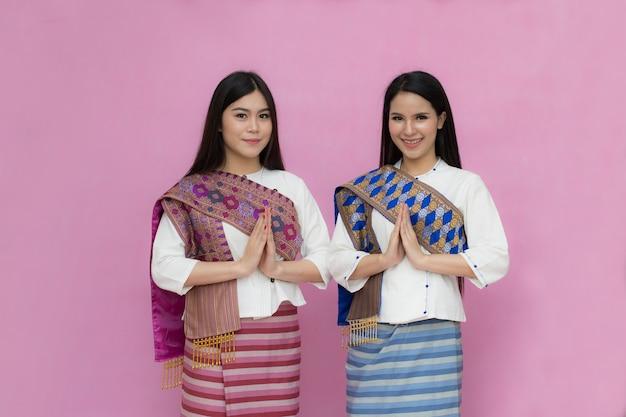 Portrait der asiatischen jungen mädchen im traditionellen thailändischen kleid, das betet