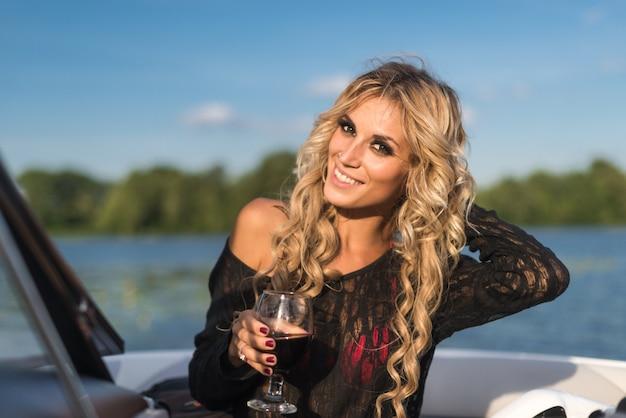 Portrait der attraktiven frau entspannenden auf yacht genießen glas wein am blauen himmel meer im freien. genuss und luxus-lifestyle