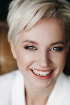 Portrait der beauitful blonden frau mit dem kurzen haar und den tiefen blauen augen