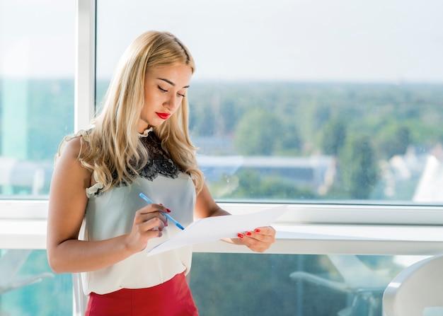 Portrait der blonden jungen geschäftsfrau, die dokument nahe dem fenster überprüft