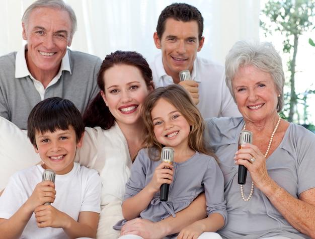 Portrait der familie, die im wohnzimmer singt