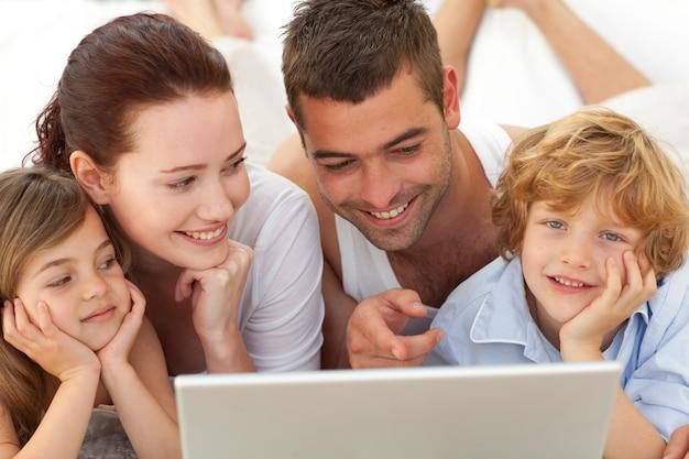 Portrait der familie im bett unter verwendung eines laptops