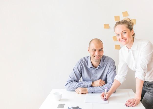 Portrait der geschäftsfrau und des geschäftsmannes, die im büro arbeiten