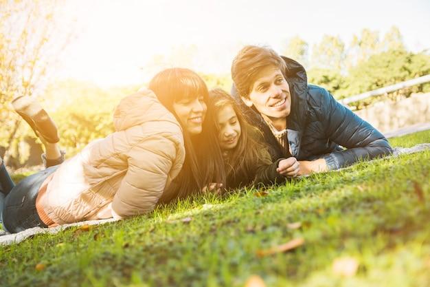 Portrait der glücklichen familie hinlegend auf gras im park