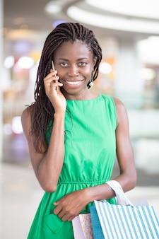 Portrait der glücklichen frau reden am telefon im shop