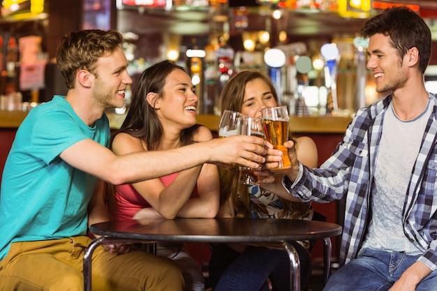 Portrait der glücklichen freunde, die mit getränk und bier rösten