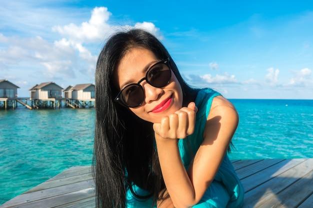 Portrait der glücklichen jungen frau auf schöne wasser-villa auf malediven insel. reisen und urlaub. außenaufnahme