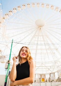 Portrait der glücklichen jungen frau, die vor riesigem ferris wheel steht