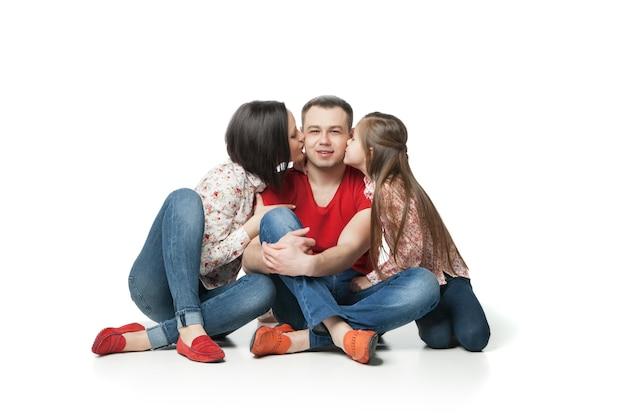 Portrait der glücklichen und freundlichen familie. hübsche kleine tochter, schöne frau und mutter, die ihren vater und ehemann küssen