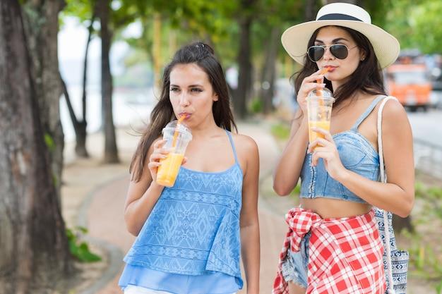 Portrait der hübschen frau zwei, die frischen saft während weg trinkt