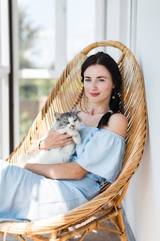 Portrait der jungen frau sitzend mit ihrer katze auf stuhl